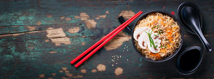 Asian noodles with vegetables and mushrooms, soy sauce, sticks on a dark background. Top view with copy space Royalty Free Stock Photo