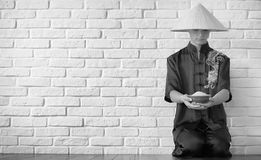 Asian novice on a white brick wall. Asian young novice on a white brick wall backgroundr stock photo