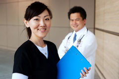 Asian nurse with doctor in background Stock Image
