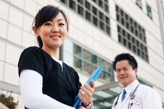 Asian nurse with doctor in background Stock Photography