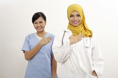 Doctor and nurse. Asian nurse and doctor with welcome hand sign on the white background Stock Photography