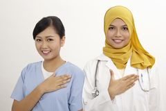 Doctor and nurse. Asian nurse and doctor with welcome hand sign on the white background Stock Photos