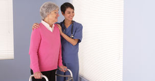Asian nurse and elderly patient standing by window Stock Images