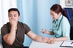Asian nurse giving vaccination injection to patient Royalty Free Stock Image