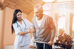 An asian nurse helps a man on an adult walker in a nursing home. An asian nurse helps a men on an adult walker in a nursing home. It`s hard for him to go Royalty Free Stock Photos