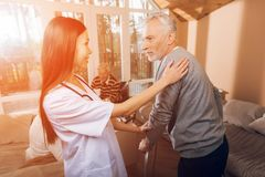 An asian nurse helps a man on an adult walker in a nursing home. An asian nurse helps a men on an adult walker in a nursing home. It`s hard for him to go Stock Images