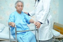 Asian nurse physiotherapist doctor care, help and support elderly old woman patient with walker. Asian nurse physiotherapist doctor care, help and support stock images