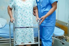 Asian nurse physiotherapist doctor care, help and support elderly old woman patient with walker. Asian nurse physiotherapist doctor care, help and support royalty free stock images