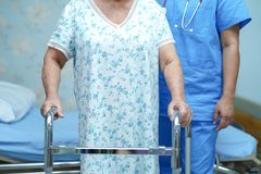 Asian nurse physiotherapist doctor care, help and support senior or elderly old lady woman patient walk with walker. Asian nurse physiotherapist doctor care stock image