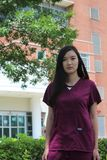 Asian Nurse Wearing Scrubs Stands in Front of Hospital. Asian nurse stands in front of a hospital wearing purple scrubs stock photography