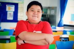 Asian obese boy standing crossed arms stock photo