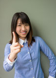 Asian office girl lifting her forefinger in grey background Stock Photos