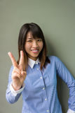 Asian office girl showing victory sign in grey background Stock Photo
