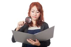 Asian office girl use magnifying glass check on a folder with ba Royalty Free Stock Image
