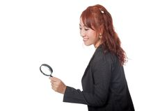 Asian office girl use magnifying glass looking down Royalty Free Stock Image