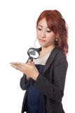 Asian office girl use magnifying glass for watching her own the Royalty Free Stock Images