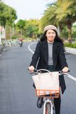 Asian office lady riding bicycle through urban area stock image