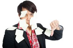 Asian office man covered in blank notes with his thumbs down. Isolated on white background royalty free stock photos