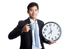 Asian office man smile with a clock and a cup of coffee Stock Photos