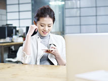 Asian office woman using cellphone Stock Photo