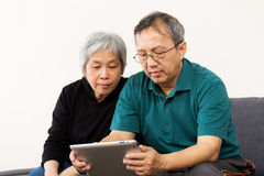 Asian old couple reading on tablet Royalty Free Stock Photo