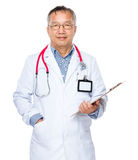 Asian old doctor with clipboard Royalty Free Stock Photos