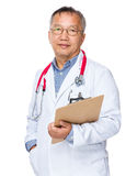 Asian old doctor holding with clipboard Royalty Free Stock Photo