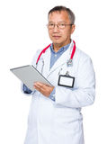 Asian old doctor use of digital tablet Royalty Free Stock Photos