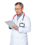 Asian old doctor use of tablet Royalty Free Stock Image
