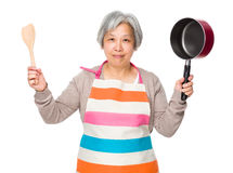 Asian old housewife holding up wooden ladle and saucepan Stock Photos