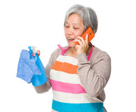 Asian old housewife talk to cellphone and usinf rag and bottle s Stock Images