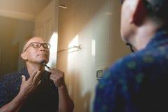 Asian old man is shaving his beard in the bathroom. Asian old man is shaving his beard in the bathroom, Mirror reflect an asian old man is shaving beard Royalty Free Stock Photo