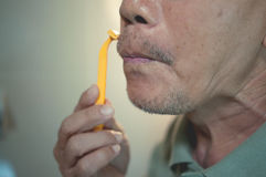 Asian old man is shaving his beard. Close up, Asian old man is shaving his beard, Vintage and retro Stock Image