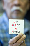 Asian Old man shows his card with AGE IS JUST A NUMBER Text Royalty Free Stock Images
