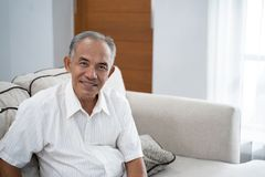 Asian old man sitting on the sofa with a smile looking at the camera. A background of window with curtain royalty free stock photography
