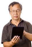Asian old man using tablet. Isolated on white background Royalty Free Stock Image