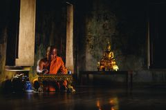 Asian Old monk thinking for writing something at Ayutthaya sanctuary temple in Thailand, about religion. stock photos