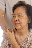 An asian old woman. Touches and holds a  hand of her young nephew Stock Photo