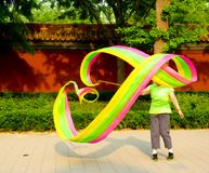 Waving Coloured ribbon. An asian old woman swinging a colourful cloth ribbon to exercise inside Jiangshan park Beijing China royalty free stock image