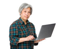 Asian old woman use of notebook computer Stock Images