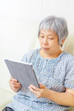 Asian old woman using tablet Stock Photo