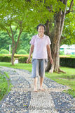 Asian older woman walking on the stone walkway Royalty Free Stock Photography