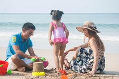 Asian parent and cute daughter made a sand castle together with