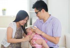 Asian parent nursing their baby stock photos
