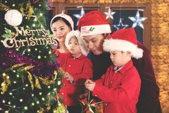 Asian parents with children decorate Christmas tree Stock Photos