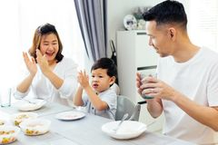 Asian parents clapping hands and giving compliment as their child does good job while having meal together at home. Asian parents clapping hands and giving Stock Image