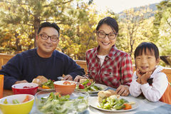 Asian parents and daughter at a table outdoors look to camera Royalty Free Stock Images