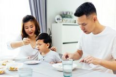 Asian parents feeding their child and the whole family having meal together at home. Asian parents feeding their child and the whole family having meal together stock photography