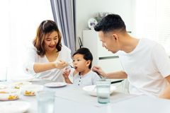 Asian parents feeding their child and the whole family having meal together at home. Asian parents feeding their child and the whole family having meal together stock images