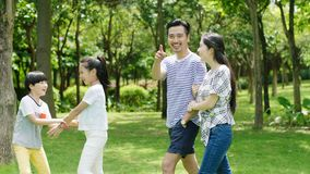 Asian family playing & laughing outdoors in park in summer. Asian parents & kids walking, playing & laughing outdoors in park in summer Stock Photography